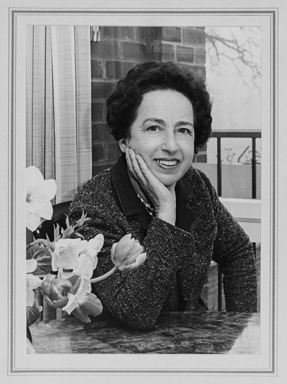 Dr. Viola Klein posing with her elbow on a table near a vase of flowers